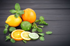 Lemon, orange and lime on a darkphone made of wood. Lemon, orange and lime with mint leaves lie on a darkphone made of wood royalty free stock images