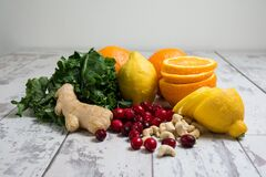 Lemon Orange Red Berries Ginger Peanut on Wooden Table Royalty Free Stock Photography