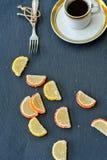 Cup of coffee and  lemon slices. Lemon and orange slices  on black slate Stock Photo