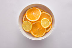 Lemon and orange slices in a white bowl on white fabric background Stock Image