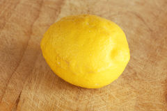 Lemon from organic farming. Detailed view of a lemon from organic farming, on a wooden cutting board, landscape cut Royalty Free Stock Image