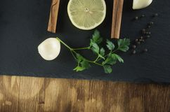 Lemon, parsley, cinnamon and garlic top view against a background of natural slate and wood. Spices and lemon lie on the background of slate and wood Royalty Free Stock Photo