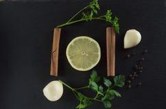 Lemon, parsley, cinnamon and garlic top view. Spices, lemon, garlic, parsley, cinnamon lie on the slate top view Royalty Free Stock Photos