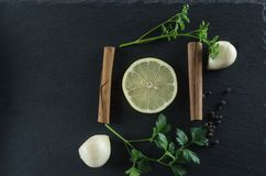 Lemon, parsley, cinnamon and garlic top view. Spices, lemon, garlic, parsley on a slate Stock Image