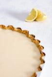 Lemon pastry tart on tablecloth with lemons Stock Image