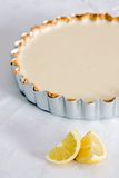 Lemon pastry tart on tablecloth with lemons. A baked lemon tart on a white tablecloth with lemons Stock Image