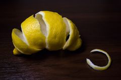Lemon peel or lemon twist on a dark brown wooden background. Close up. Citrus limon stock image