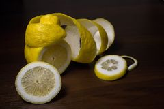 Lemon peel or lemon twist on a dark brown wooden background. Lemon slices are cut across. Close up. Citrus limon stock images
