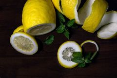 Lemon peel or lemon twist on a dark brown wooden background with a sprig of fragrant, green mint. Lemon slices are cut across. Clo. Se up. Top view. Citrus limon stock images