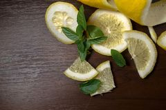 Lemon peel or lemon twist on a dark brown wooden background with a sprig of fragrant, green mint. Lemon slices are cut across. Clo. Se up. Top view. Citrus limon royalty free stock images