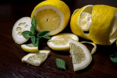 Lemon peel or lemon twist on a dark brown wooden background with a sprig of fragrant, green mint. Lemon slices are cut across. Close up. Citrus limon. Mentha royalty free stock images
