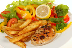 Lemon pepper chicken and fries Stock Images