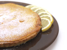 Lemon pi. A lemon pie served in a brown plate with a few slices of lemon royalty free stock images