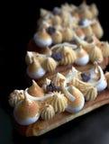 Lemon pie eclairs with purple crumble, citrus ganache and meringue close up royalty free stock photos