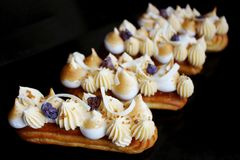Lemon pie eclairs with purple crumble, citrus ganache and meringue side view royalty free stock photography