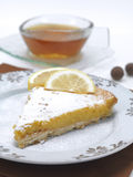 Lemon pie and hot tea. A portion of a lemon pie served in a traditional plate with a cup of hot tea and two chocolate balls stock image