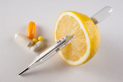 Lemon, pills , vitamins with thermometer   on white background Royalty Free Stock Photo