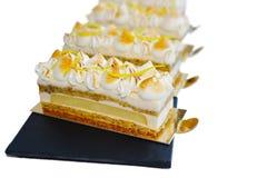 Lemon and pistachio cake slices on golden coasters stock image