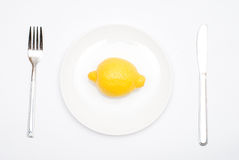 Lemon on the plate. With a fork and knife Stock Photo