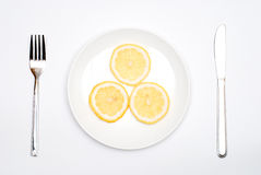 Lemon on the plate. Slice Lemon on the plate with a fork and knife Stock Photo