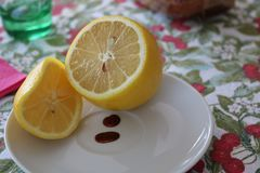 Lemon in a plate. Yellow lemon slice in a plate on a table Royalty Free Stock Photo