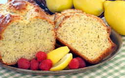 Lemon Poppyseed Pound Cake. Freshly baked lemon poppyseed pound cake on a cake with ripe raspberries and lemon slices Royalty Free Stock Image
