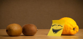 Lemon with post-it note laughing on kiwis. Lemon with sticky post-it note gesturing to kiwis stock photography