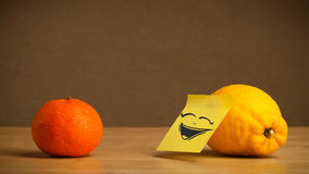 Lemon with post-it note laughing on orange Stock Images