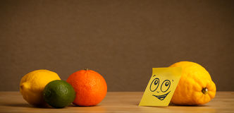 Lemon with post-it note looking at citrus fruits Stock Photography