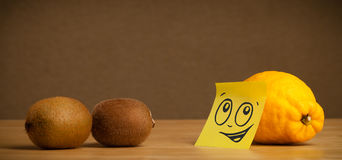 Lemon with post-it note looking at kiwis Stock Photo