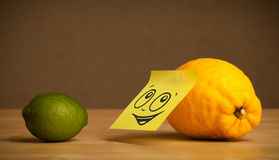 Lemon with post-it note looking at lime Stock Photography