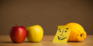 Lemon with post-it note smiling at apples Stock Photography