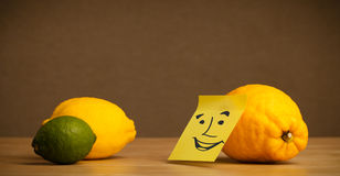 Lemon with post-it note smiling at citrus fruits Royalty Free Stock Image