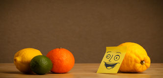 Lemon with post-it note smiling at citrus fruits Royalty Free Stock Photo