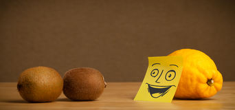 Lemon with post-it note smiling at kiwis Royalty Free Stock Images