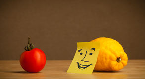 Lemon with post-it note smiling at tomato Stock Images