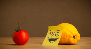 Lemon with post-it note smiling at tomato Stock Photography
