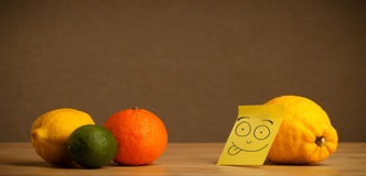 Lemon with post-it note sticking out tongue to citrus fruits Stock Photography