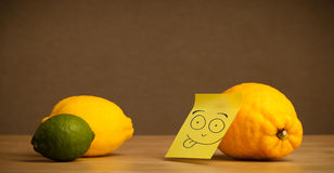 Lemon with post-it note sticking out tongue to citrus fruits Stock Photo