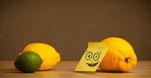 Lemon with post-it note watching at citrus fruits Royalty Free Stock Photography