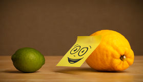 Lemon with post-it note watching at lime Royalty Free Stock Photos
