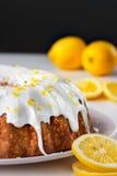 Lemon pound bundt cake. With white frosting on plate with fresh lemons Royalty Free Stock Photo