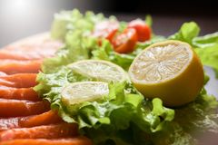 Lemon with red fish and salad and cherry pickers stock photography