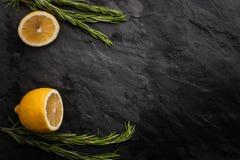 Lemon and rosemary on the black stone table Royalty Free Stock Photo