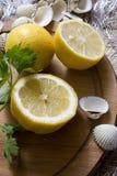 Lemon and seashells. Fresh lemon on a wooden board and seashells Royalty Free Stock Image