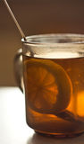 Lemon segment in a tea cup. The lemon segment swims in a tea cup Royalty Free Stock Images
