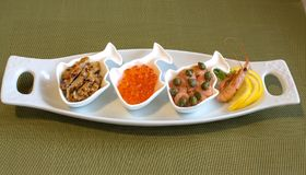 Three small portions of seafood. stock images