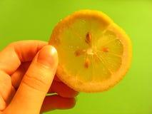 Lemon Slice. Hand holding a lemon slice next to a vibrant green background Stock Photo