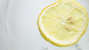 Lemon slice drop into water stock video footage