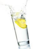 Lemon slice splash. Lemon slice falling into glass of water with splash royalty free stock images